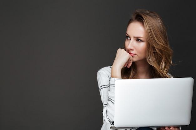 Ernstige dame die laptop over donkere muur met behulp van