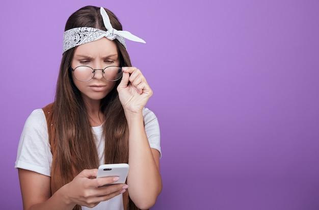 Ernstige dame in glazen met een telefoon in haar handen.