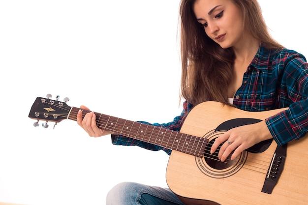 Ernstige dame met gitaar in handen met gesloten ogen geïsoleerd op witte achtergrond