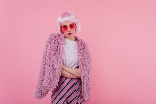 Ernstige dame met roze haar poseren met gekruiste armen. binnen schot van lief meisje in bontjasje en zonnebril