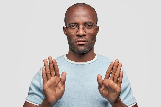 Ernstige donkere huid man toont stop gebaar