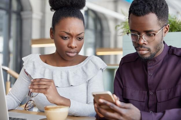 Ernstige donkere huidskleurige vrouwelijke en mannelijke zakenpartners controleren melding op slimme telefoon, werken aan rapport op laptopcomputer, zitten in coffeeshop hebben geconcentreerde blikken.