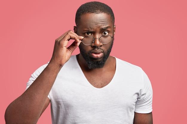 Ernstige, donkere mannelijke professor kijkt verbijsterd door een bril