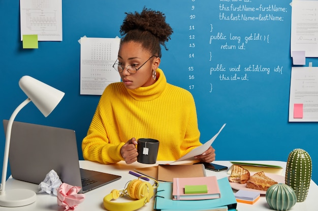 Ernstige donkerhuidige vrouw controleert informatie van papieren en laptop, kijkt naar trainingswebinar over computerprogrammering