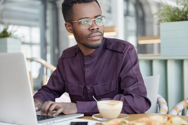 Ernstige doordachte donkere zakenman gericht op werkkwesties, toetsenbordinformatie op laptopcomputer