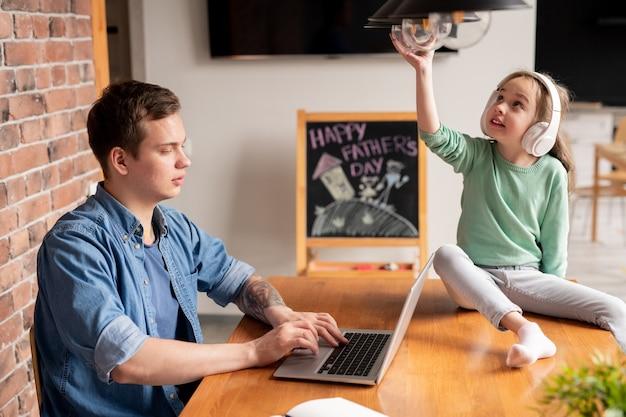 Ernstige drukke hipster jonge vader met tatoeage aan tafel zitten en werken met laptop thuis, terwijl zijn dochter hoofdtelefoon zittend op tafel en lamp draaien