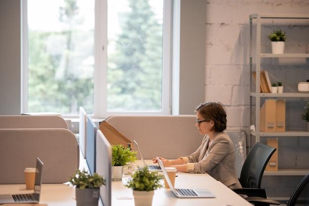 Ernstige drukke jonge dame met kort haar, zittend aan tafel in moderne kantoren en met behulp van laptop tijdens het analyseren van de verkoopprognose