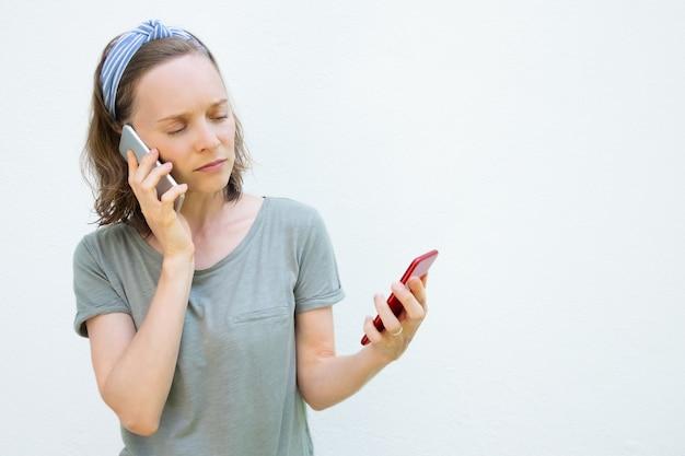 Ernstige drukke jonge vrouw met behulp van twee mobiele telefoons