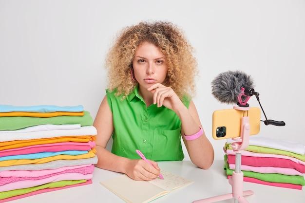 Ernstige drukke vrouw schrijft informatie op, luistert naar livestreamvideo en zit aan een witte tafel voor de telefooncamera