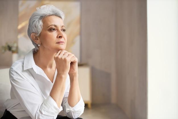 Ernstige elegante gepensioneerde vrouw met kort kapsel poseren binnenshuis met handen onder de kin, wegkijken met peinzende gezichtsuitdrukking, nadenken over een idee of beslissing
