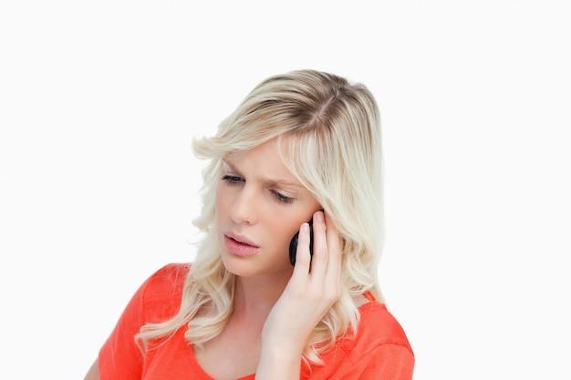 Ernstige en aantrekkelijke vrouw die op cellphone spreekt