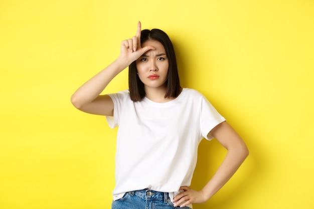 Ernstige en arrogante aziatische vrouw die het verloren team bespot, een verliezersteken op het voorhoofd toont en zelfverzekerd naar de camera kijkt, staande over een gele achtergrond.