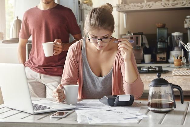 Ernstige en geconcentreerde jonge vrouw in glazen met mok in de ene hand en pen in de andere, gericht op papierwerk