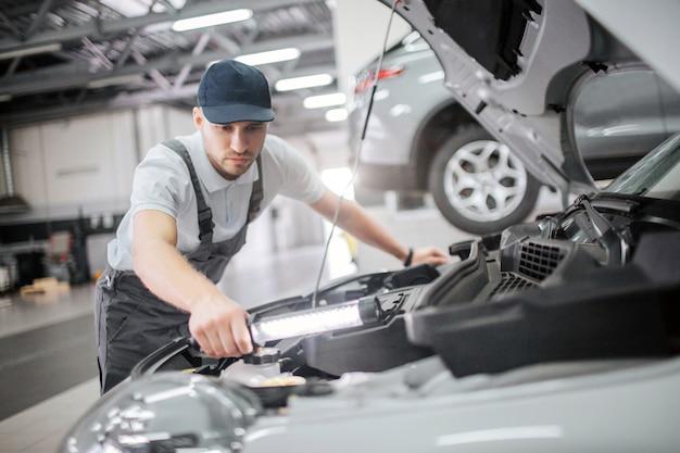 Ernstige en geconcentreerde man staat bij geopende carrosserie en repareert details erin. hij is kalm en geconcentreerd. man houdt sleutel in de hand. hij gebruikt het.