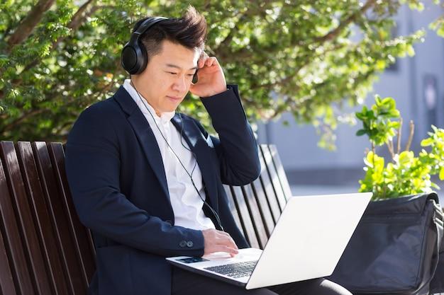 Ernstige en gefocuste jonge aziatische man die video-inhoud bekijkt op een laptop die op een bank zit in een zakenman in een pak met een grote koptelefoon
