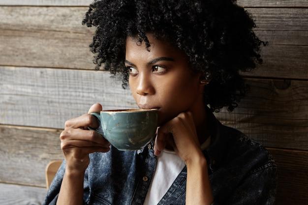 Ernstige en peinzende jonge donkere vrouw student met krullend haar gekleed in stijlvol denim shirt met grote mok koffie, genieten van verse ochtend cappuccino voor lezingen op de universiteit