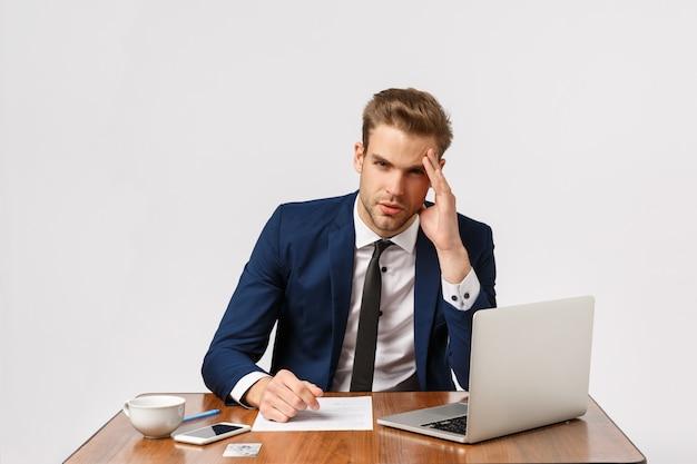 Ernstige en vermoeide jonge workaholic, zakenman in kantoor voelt duizelig en verdrietig, werkt de hele dag, zit met laptop, documenten en koffie, raakt tempel aan, heeft hoofdpijn