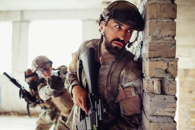 Ernstige en voorzichtige man leunt tegen de muur.