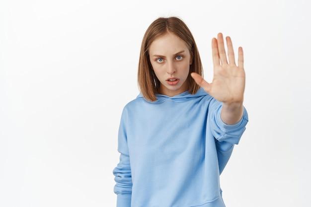 Ernstige en zelfverzekerde blonde vrouw strekt haar hand uit, laat een afwijzingsgebaar zien, zeg nee, verbied slechte actie, waarschuw je, staande tegen een witte muur