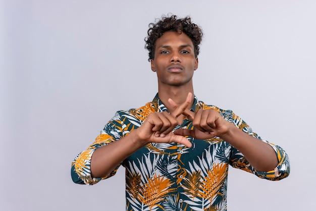 Ernstige en zelfverzekerde jonge knappe donkerhuidige man met krullend haar in bladeren bedrukt hemd maken teken kruising vingers vormen een x op een witte achtergrond