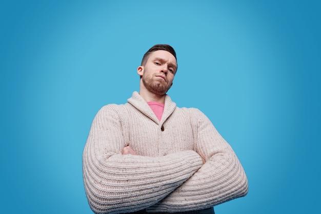 Ernstige en zelfverzekerde jonge man in vrijetijdskleding die de armen op de borst kruist terwijl hij geïsoleerd staat