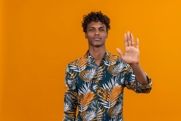 Ernstige en zelfverzekerde knappe man in bladeren bedrukt hemd hand in hand in stop of genoeg gebaar met afkeer op een oranje achtergrond