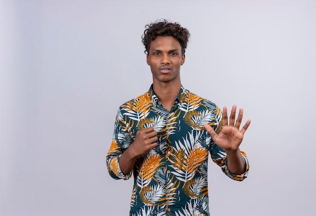 Ernstige en zelfverzekerde knappe man in bladeren bedrukt overhemd hand in hand in stop of genoeg gebaar uiting van afkeer op een witte achtergrond