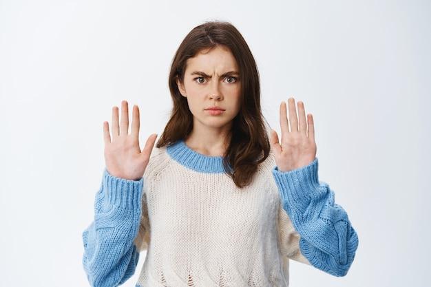 Ernstige en zelfverzekerde vrouw fronst, steekt handen op in blokgebaar en zegt nee, keur slechte actie af, probeert te waarschuwen of te weigeren, staande tegen een witte muur