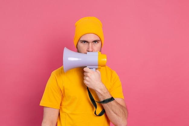 Ernstige europese man met megafoon op roze achtergrond
