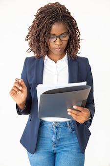 Ernstige expert die een bril draagt, document leest