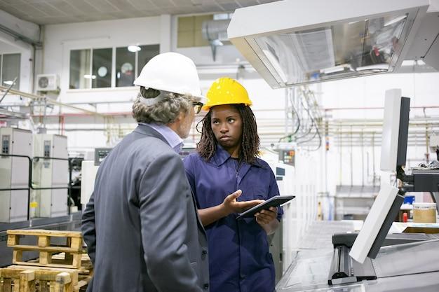 Ernstige fabrieksarbeider praten met baas op machine op fabrieksvloer, wijzend op tabletscherm
