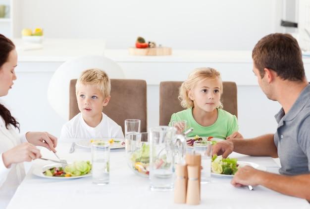 Ernstige familie die een salade eet tijdens de lunch in de keuken
