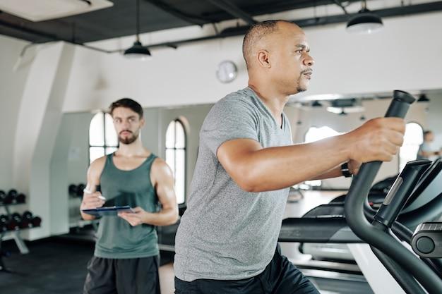 Ernstige fitte trainer die aantekeningen maakt bij het kijken naar zijn volwassen cliënt die in een elliptische machine loopt