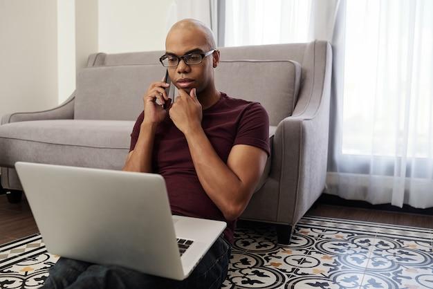 Ernstige freelancer zijn kin wrijven tijdens het telefoneren met de klant en het lezen van het contract op het laptopscherm
