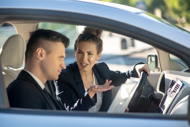 Ernstige gebaren vrouw rijden en een man in een auto