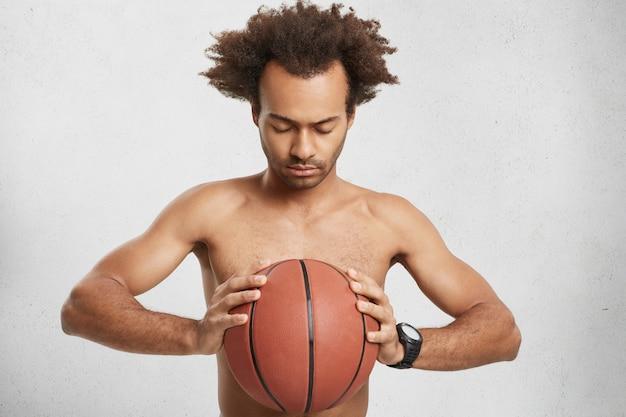 Ernstige geconcentreerde basketbalspeler houdt bal vast, bidt voor geluk tijdens het spel