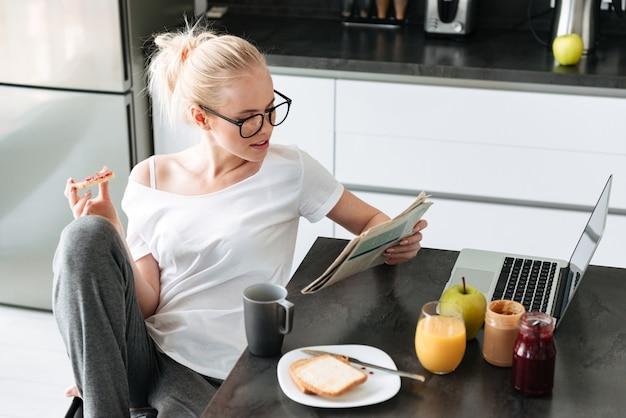 Ernstige geconcentreerde dame die krant leest terwijl ontbijt