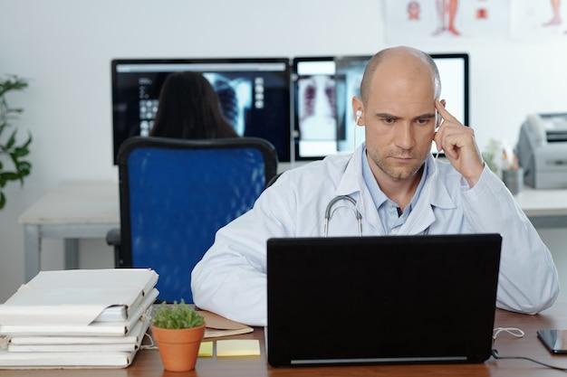 Ernstige geconcentreerde huisarts die oortelefoons draagt tijdens het kijken naar webinar op laptop, zijn collega werkt op de achtergrond