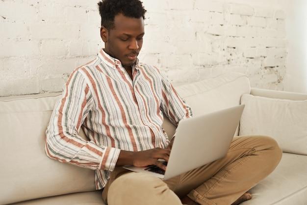 Ernstige geconcentreerde jonge donkere zakenman zittend op de bank met draagbare computer op zijn schoot, typen, online werken vanuit huis