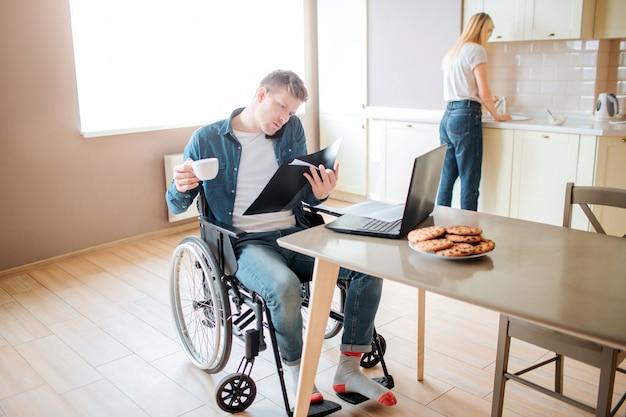 Ernstige geconcentreerde jonge student met inclusiviteit en gehandicapten. studeren en praten over de telefoon. kopje koffie vasthouden. jonge vrouw afwas in gootsteen. samenwerken.