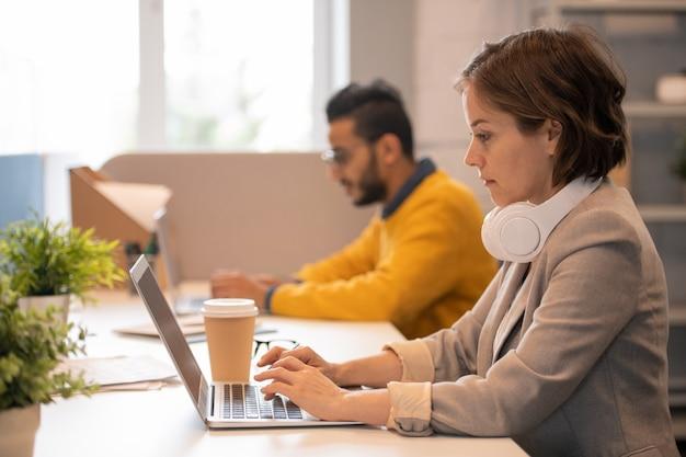 Ernstige geconcentreerde jonge vrouw met koptelefoon op nek aan tafel zitten en typen op laptop in kantoor