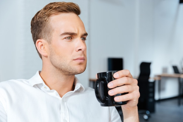 Ernstige geconcentreerde jonge zakenman die koffie drinkt op kantoor