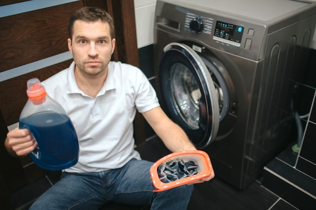 Ernstige geconcentreerde kerel die in badkamers vloeibaar poeder houdt. zit op knieën naast gefrustreerde wasmachine.