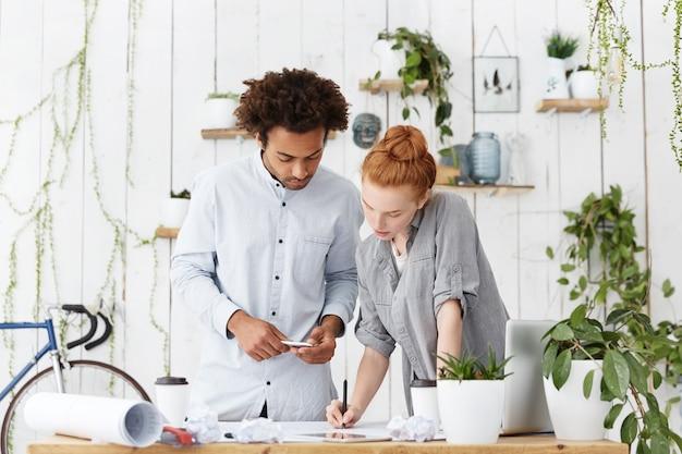 Ernstige geconcentreerde man en vrouw staan in de buurt van een bureau omringd met moderne apparaten