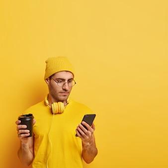 Ernstige geconcentreerde man houdt mobiele telefoon vast, leest nieuws op internet, gekleed in gele hoed en t-shirt, geniet van aromatische drank, verbonden met gratis wifi