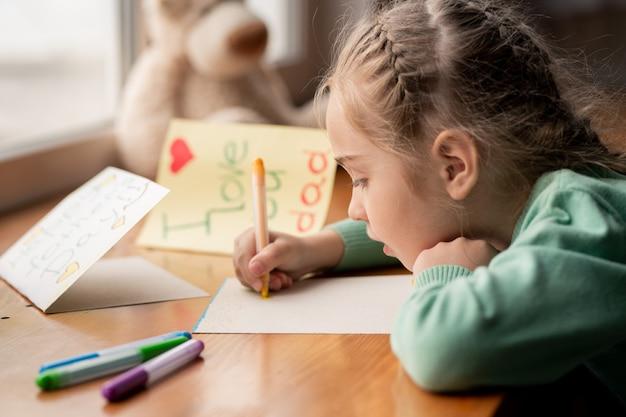 Ernstige geconcentreerde meisje met gevlochten haar, leunend op houten tafel en briefkaart maken voor papa op vaders dag