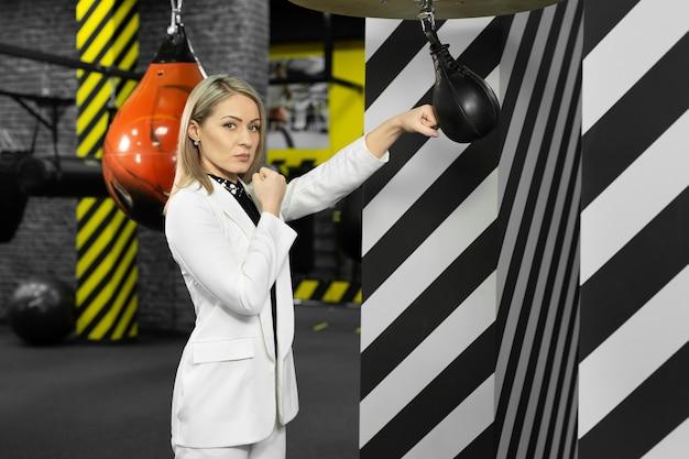 Ernstige, gefocuste zakenvrouw raakt een bokszak in de sportschool. het concept van woedebeheersing.
