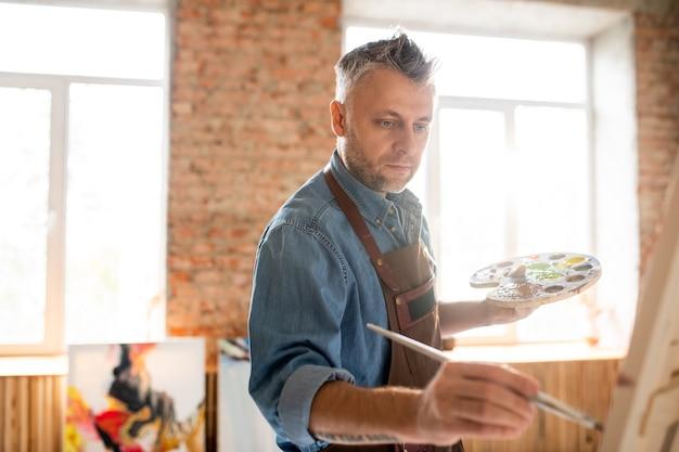 Ernstige geïnspireerde man met palet en penseel staande voor ezel en schilderen in werkplaats of atelier