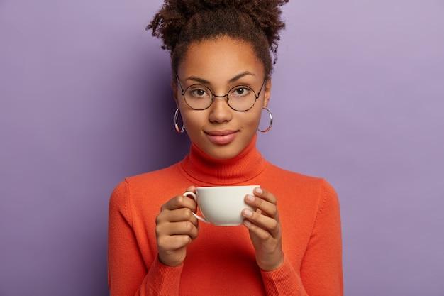 Ernstige gekrulde vrouw in bril geniet van warme drank bij koud weer, houdt witte kopje thee, gekleed in oranje poloneck, kijkt direct naar de camera, vormt binnen