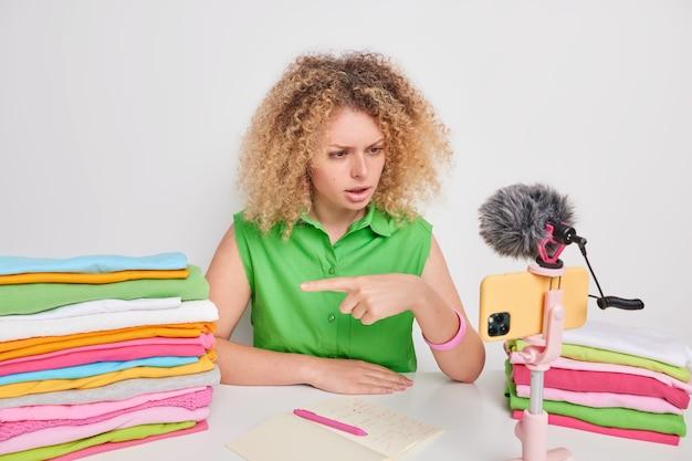Ernstige gekrulde vrouwelijke vlogger wijst naar stapel veelkleurige opgevouwen was gekleed in groen t-shirt praat over wasverzachter voor je was zit aan tafel geeft advies over het kiezen van wasmiddel